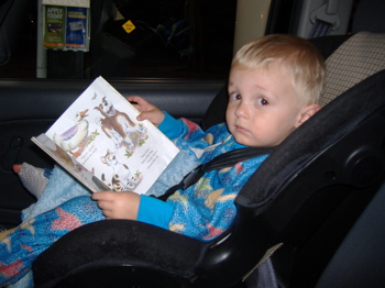 Tristen reading in his carseat.